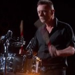 Larry seemingly winces while playing drums at the Academy Awards.
